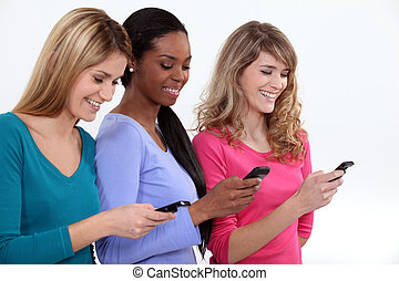 Three female students texting.