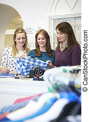 Three Female Voluntary Workers In Charity Shop