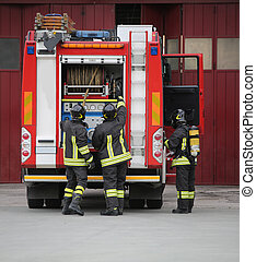 three firemen in action and the fire engine