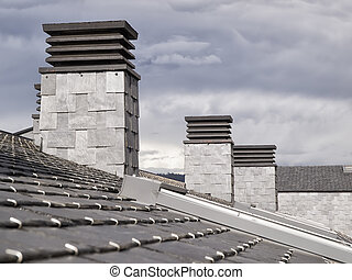 Three fireplaces on a slate roof in a cloudy day.