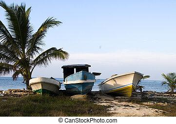 three fishing boats on shore caribbean sea