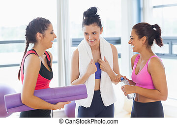 Three fit young women chatting in exercise room