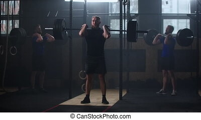Three fitness man bodybuilder training using barbell weightlifting exercise muscular sportsman power lifting heavy weight doing squats in gym practice enjoying healthy lifestyle.