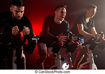 three fitness men on gym bicycle, training on a stationary bike in health club