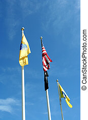 Three flags against blue sky