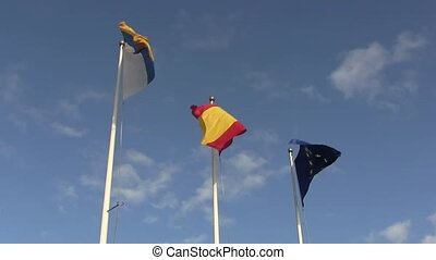 Three flags blowing in the wind.