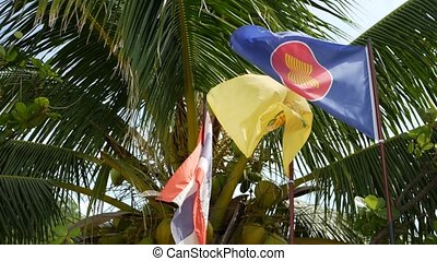 Three flags waving against tropical leaves. Symbol of ASEAN fluttering near flags of Thailand and Thai King against green leaves of exotic palm trees on windy day. Community of asian nations concept.