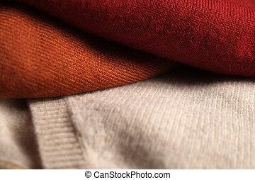 Three folded woolen sweaters