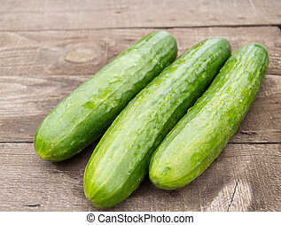 Three fresh cucumber lying on an old wooden background
