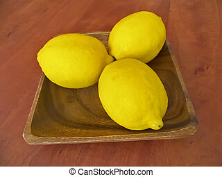 Three fresh lemons on a wooden plate