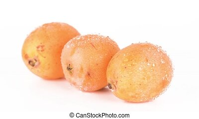 Japanese loquats - Three fresh orange Japanese loquats stack...