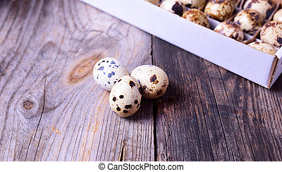 Three fresh quail eggs on a gray wooden surface