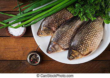 Three fresh raw crucian on a wooden background with herbs. Top view