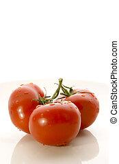 three fresh tomatos on a white background