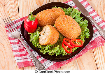 three fried breaded cutlet with lettuce on a black plate and wooden background