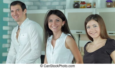 Three friends are preparing themselves healthy dinner and smiling directly at the camera
