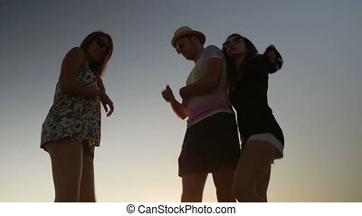 Three friends dancing on the beach at sunset
