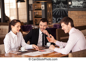 Three friends discuss graph lying on table at cafe. Business...