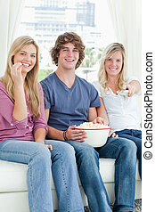 Three friends eating popcorn while smiling and using the tv remote to change the channel