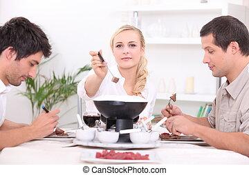 Three friends enjoying chocolate fondue