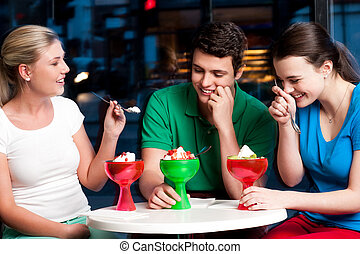 Three friends enjoying tempting dessert