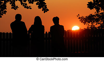 Three friends enjoying the sunset