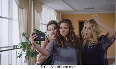 Three friends fool around in front of the camera, showing a fashionable pose to look better in pictures. They have a stylish hairstyle and natural, make-up, suitable for any event - wedding, birthday