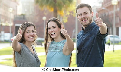 Three friends gesturing thumb up at camera - Front view of...