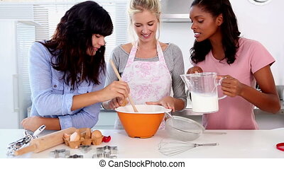 Three friends home baking together in the kitchen