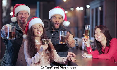 Three friends in Santa hats and the girl behind the bar with a glass of beer