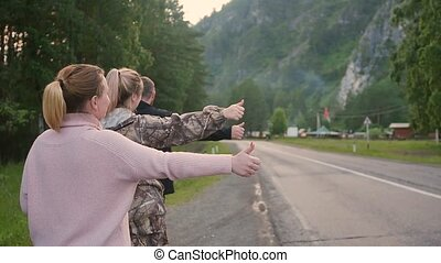 three friends in the daytime are hitchhiking with two lanes, sticking out a thumb. a company of tourists wants to stop the car. Slow motion.
