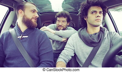 Three friends laughing in car