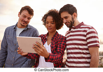 Three friends looking at a tablet