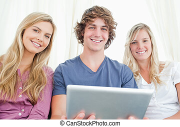 Three friends looking at the camera while holding a tablet