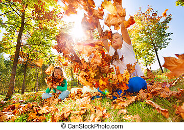 Three friends playing with leaves in the forest