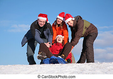 three friends push girl on sled