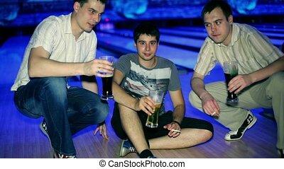 Three friends sit and drink bear in dark bowling club
