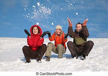 three friends sit on snow and throw snows