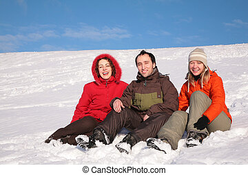 three friends sit on snow on hillside
