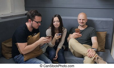 Three friends sit on sofa in studio and play with smartphones.
