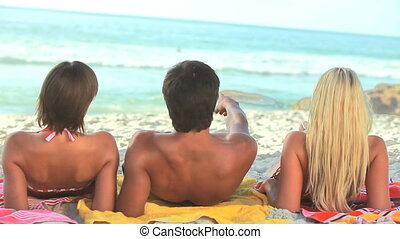 Three friends sit on their towels on the sand