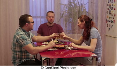 Three friends sitting at the table and dinner