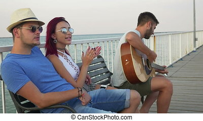Three friends sitting on a bench with the sea as a background and singing with a guitar