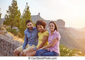 Three friends sitting on a stone wall