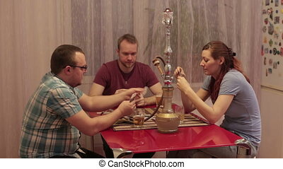 Three friends smoke shisha and talking