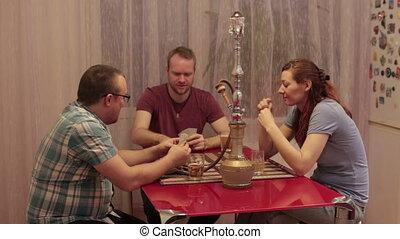 Three friends smoking shisha and playing cards