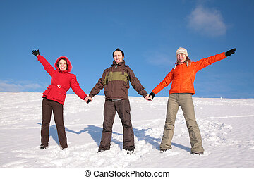 three friends stand on snow on hillside