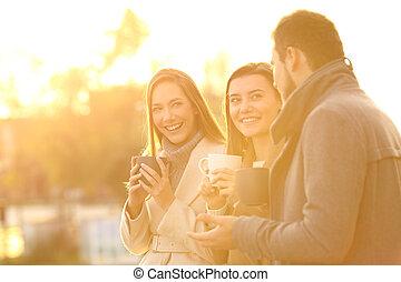 Three friends talking at sunset in winter
