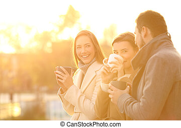 Three friends talking outdoors at sunset