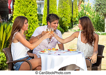 Three friends toasting while having lunch outdoors